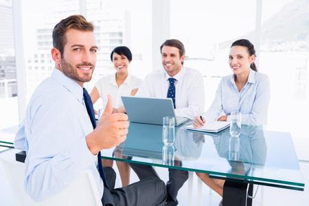 Retrato de un ejecutivo haciendo un gesto pulgar hacia arriba con los reclutadores durante una entrevista de trabajo en la oficina