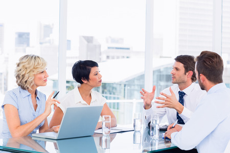 Smartly dressed young executives sitting around conference table in office photo