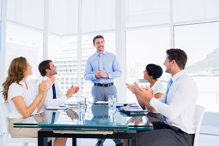 Business executives clapping around conference table in a bright office photo