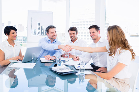 Smartly dressed executives shaking hands during a business meeting in the office Stock Photo