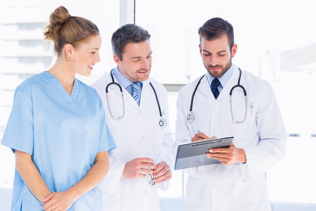 Two male doctors and female surgeon reading medical reports at the hospital photo