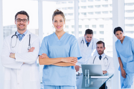 Portrait of doctors with colleagues using laptop behind in a medical office photo