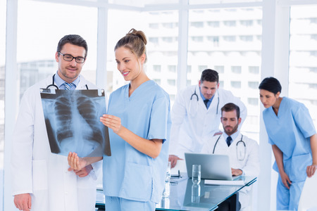 Smiling doctors examining x-ray with colleagues using laptop behind in a medical office photo
