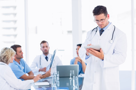 Doctor using digital tablet with colleagues in meeting at a medical office photo