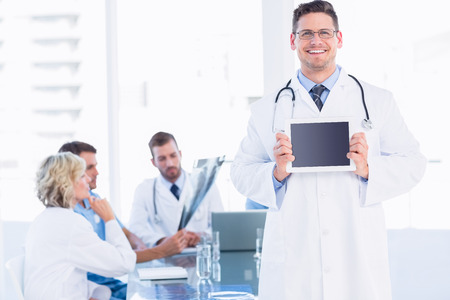 Doctor holding digital tablet with colleagues in meeting at a medical office photo