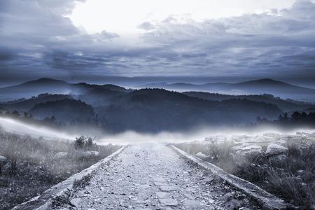 Stony path leading to large misty mountains Stock Photo