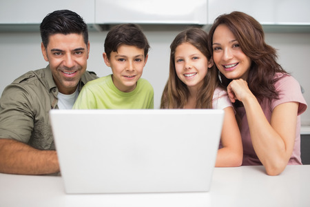 Portrait of a smiling couple with young kids using laptop at home photo