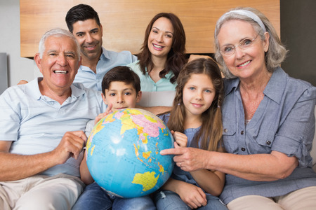 Portrait of an extended family sitting on sofa with globe in the living room at home photo