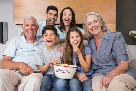 Portrait of happy extended family watching tv on sofa in the living room at home
