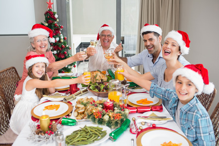 glass christmas tree ornament: Happy family in santas hats toasting wine glasses at dining table in the house Stock Photo