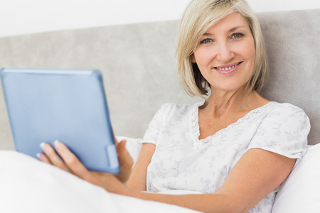 mature adult: Portrait of a smiling mature woman using digital tablet in bed at home