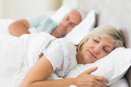 pareja durmiendo: Primer plano de una pareja madura durmiendo con los ojos cerrados en la cama en su casa