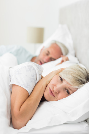 snoring: Closeup of a woman covering ears while man snoring in bed at home