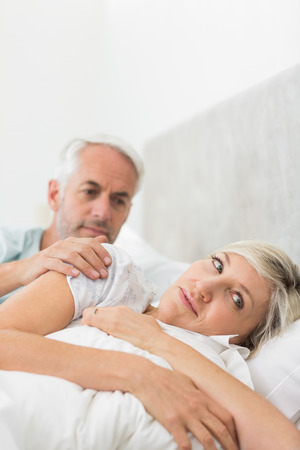 Woman ignoring mature man while lying in bed at the home photo