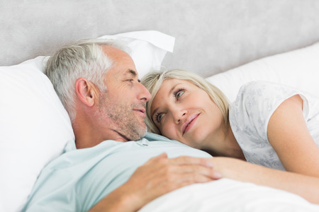 Closeup of a loving mature man and woman lying in bed at the home photo