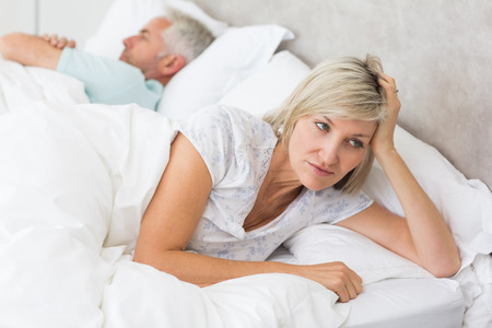 Closeup of a tensed woman lying besides man in bed at home photo