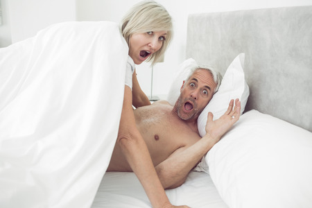 Portrait of a mature couple shouting in bed at home photo