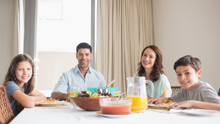 Portrait of happy family of four sitting at dining table in the home photo