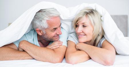Close-up portret van een volwassen paar liggend in bed thuis