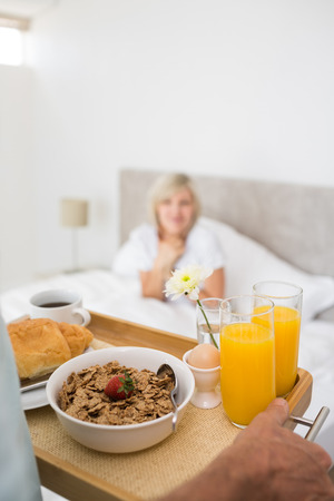 Happy mature woman sitting in bed with breakfast in foreground at home photo