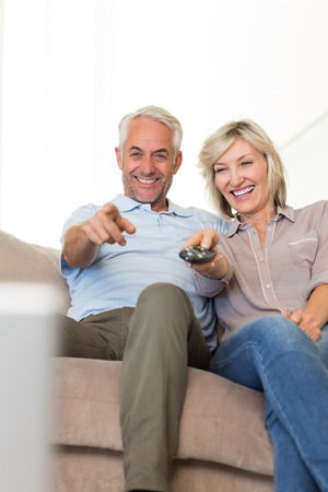 Happy mature couple watching tv on sofa at home photo