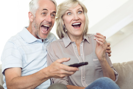 pareja viendo tv: Alegre pareja madura viendo la televisi�n en el sof� en casa
