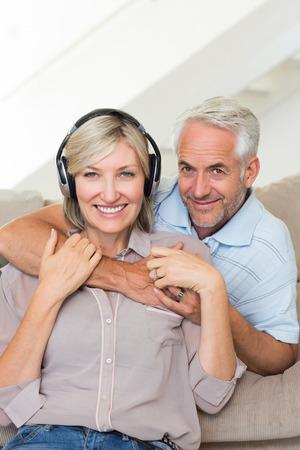 mujer de espaldas: Sonriente hombre maduro abrazando a la mujer desde atr�s en el sof� en casa Foto de archivo