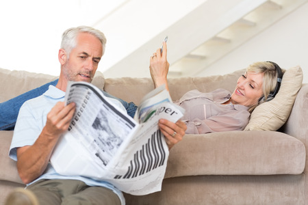 Mature man reading newspaper while woman text messaging in the living room at home photo
