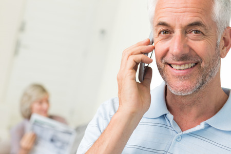 Closeup of a mature man using cellphone with woman reading newspaper in background at home photo