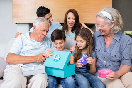 Cheerful extended family sitting on sofa with gift boxes in the living room at home photo