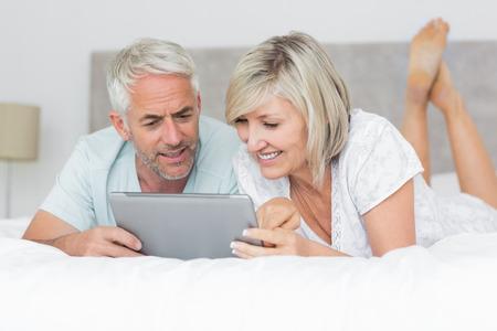pareja en casa: Sonriente pareja madura que usa la tableta digital en la cama en su casa