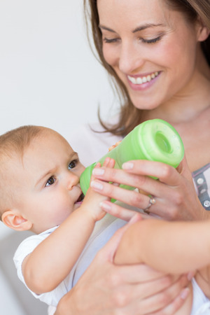 Closeup of a mother feeding baby with milk bottle at home photo