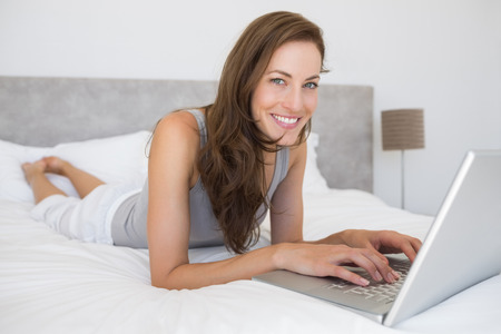 woman laptop: Portrait of a relaxed young woman using laptop in bed at home Stock Photo