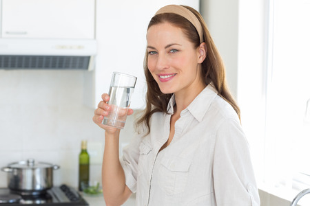 Portrait of a young woman drinking water in the kitchen at home photo