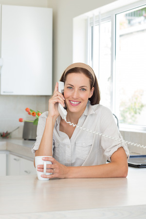 Portrait of a smiling young woman with coffee cup using landline phone in the kitchen at home photo