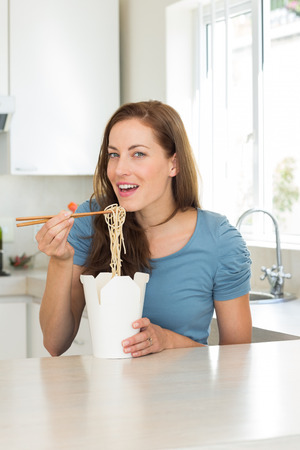 Portrait of a smiling young woman eating noodles in the kitchen at home photo