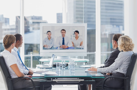 business: Business team having video conference with another business team in office Stock Photo