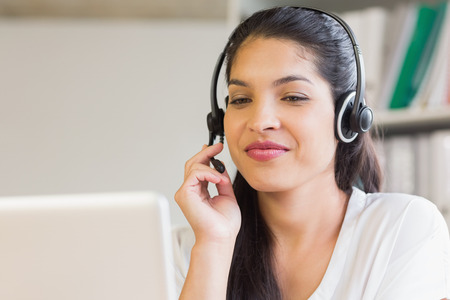 Attractive businesswoman using headset in office photo