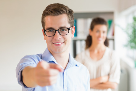 Portrait of confident businessman pointing while colleague standing in background at office photo