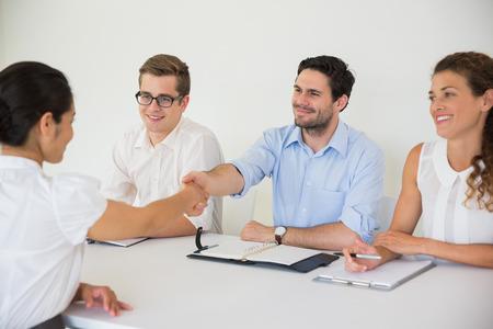 interview job: La gente de negocios d�ndose la mano durante la reuni�n de la contrataci�n laboral en la oficina