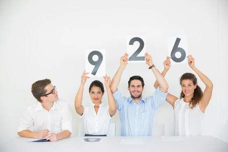 Portrait of business people holding score signs at desk in office photo