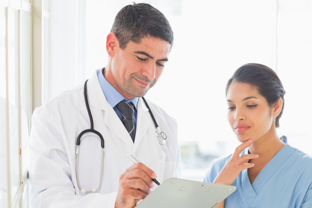 Male doctor writing in clipboard while nurse standing by in hospital photo