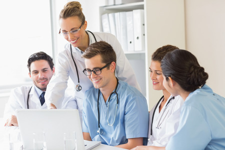male nurse: Smiling doctors and nurses discussing over laptop in hospital Stock Photo
