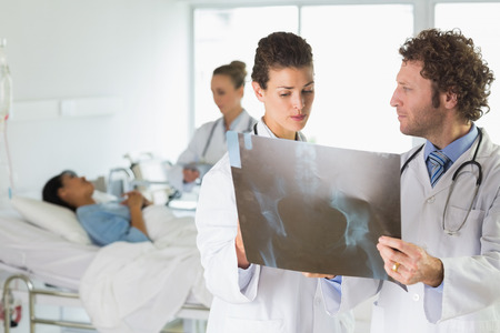 Doctors examining Xray with colleague and patient in background at hospital photo