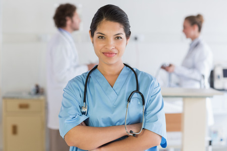 Portrait of confident female nurse  with doctors in background at hospital  photo