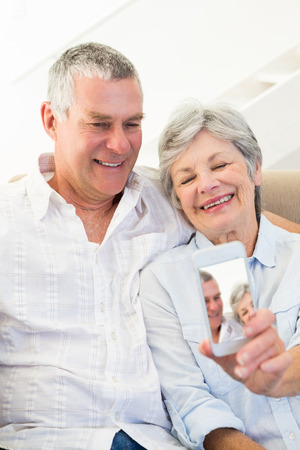 Smiling senior couple taking picture through mobile phone at home photo