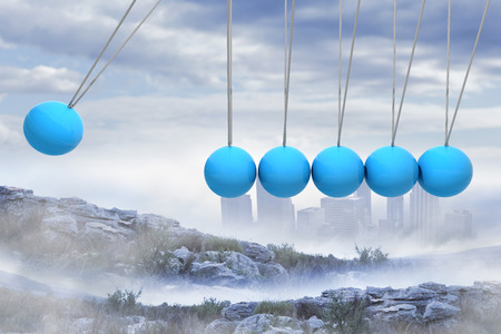 newton's cradle: Newtons cradle above city in mountains