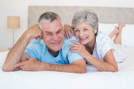 Portrait of loving senior couple lying in bed at home photo