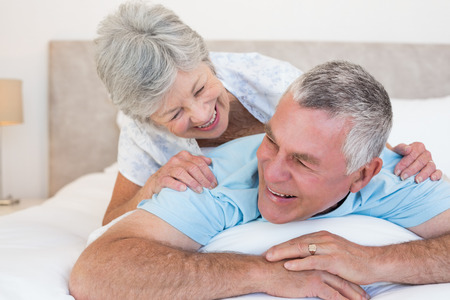 Happy senior couple lying in bed at home photo