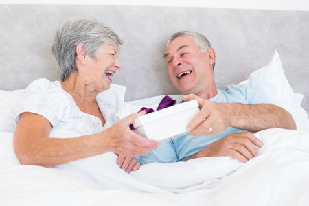 Happy senior couple holding gift box while relaxing in bed at home photo